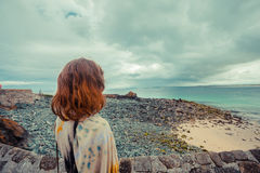 Young woman standing on the coast Royalty Free Stock Photos