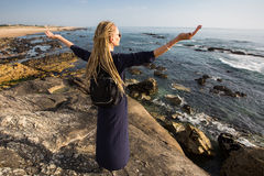 Young woman standing on coastal rocks towards the ocean surf. Stock Images