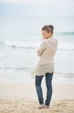 Young woman standing on cold beach Stock Photo