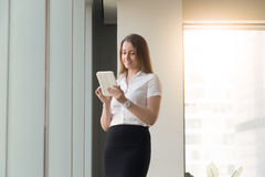 Young woman standing with computer tablet in hands. Smiling woman standing with computer tablet in hands. Happy female reading Internet news, entertains with Royalty Free Stock Photo