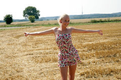 Young woman standing in a cornfield. Young blonde woman standing on a mown cornfield Stock Images