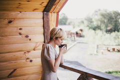 Young woman standing on the cozy balcony with a cup of tea Royalty Free Stock Photo