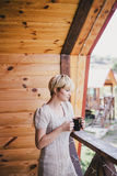 Young woman standing on the cozy balcony with a cup of tea Royalty Free Stock Image