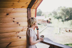 Young woman standing on the cozy balcony with a cup of tea Stock Image