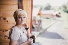 Young woman standing on the cozy balcony with a cup of tea Royalty Free Stock Photography