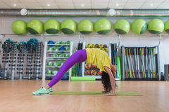 Young woman standing in crab posture on mat in fitness studio while practicing yoga exercises stock photos