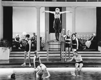 Young woman standing on a diving board surrounded by a group of people playing. (All persons depicted are no longer living and no estate exists. Supplier grants stock photo