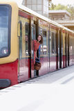 Young woman standing in door of train wagon Royalty Free Stock Images