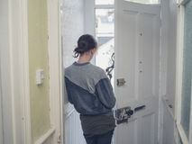 Young woman standing in doorway. A young woman is standing in a doorway at home Royalty Free Stock Photography