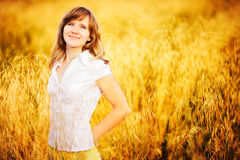 Young woman standing in dry grass field Stock Photography