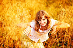 Young woman standing in dry grass field Royalty Free Stock Images
