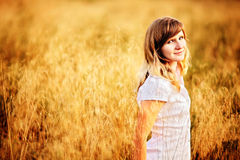 Young woman standing in dry grass field Royalty Free Stock Photos