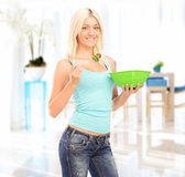 Young woman standing and eating a salad Royalty Free Stock Photography