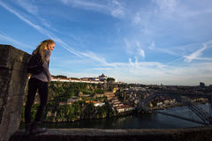 Young woman standing enjoying view of Douro river and Dom Luis I bridge, Porto. Royalty Free Stock Photos