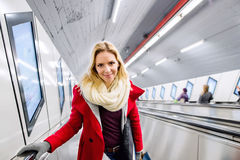 Young woman standing at the escalator in Vienna subway. Beautiful young blond woman in red coat standing at the escalator in Vienna subway Royalty Free Stock Photos