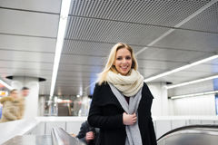 Young woman standing at the escalator in Vienna subway. Beautiful young blonde woman in black coat and big woolen scarf standing at the escalator in Vienna Stock Photo