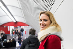 Young woman standing at the escalator in Vienna subway. Beautiful young blonde woman in red coat and big woolen scarf standing at the escalator in Vienna subway Stock Image