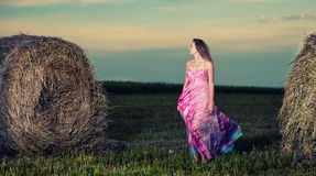 Young woman standing in evening field over haystack. Fashion sty Royalty Free Stock Image