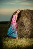 Young woman standing in evening field over Stock Photos