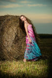 Young woman standing in evening field over Royalty Free Stock Image