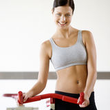 A young woman standing by an exercise bike Stock Image