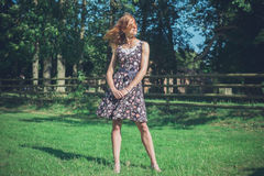 Young woman standing in field by fence on summer day Royalty Free Stock Images