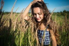 Young woman standing on a field of grass in summer day. Beautiful girl is correcting hairstyle on background of nature Stock Photos