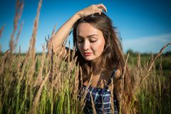Young woman standing on a field of grass in summer day. On nature background. Beautiful girl enjoying summertime Stock Photos
