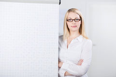 Young Woman Standing By Flip Chart. Portrait of confident young woman standing by flip chart in office royalty free stock photography
