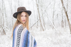 Young woman standing in forest cover with snow. Young woman in the snow wearing a bohemian style blanket and hat during a winter storm Royalty Free Stock Photography
