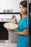 Young woman standing by fridge with bowl of popcorn, smiling, portrait Royalty Free Stock Photo