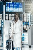 Young woman standing in front of Destination digital board in airport. royalty free stock photo