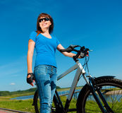 Young woman is standing in front of her bicycle Stock Image