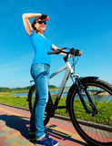 Young woman is standing in front of her bicycle Stock Photos