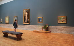 Young woman standing in front of masterpieces,Cleveland Art Museum,Ohio,2016. Young lady in colorful print dress, standing in front of several masterpieces royalty free stock photos
