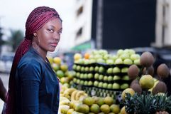 Young woman standing in front of shelves of fruit to the market. Young woman standing in front of shelves of fruit, looking at the camera Royalty Free Stock Photography