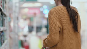 Young woman standing in front of shelves in the supermarket and holding shampoo. Then puts bottle in shopping cart. 4K stock footage