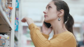 Young woman standing in front of supermarket shelves, holding phone and talking. Takes the item and asking advice. 4K stock video