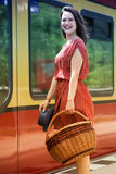 Young woman standing in front of train at station Royalty Free Stock Photo