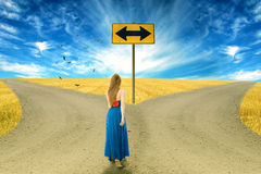 Young woman standing in front of two roads royalty free stock photos