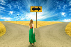Young woman standing in front of two roads Stock Photo