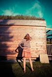 Young woman standing in garden outside cabin Royalty Free Stock Photography