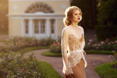 Young woman standing on garden terrace and leaning on balustrade. Blonde woman with elegant hairstyle wearing dress and white lace jacket, standing on garden stock photo