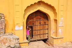 Young woman standing by the gate in Amber Fort near Jaipur, Rajasthan, India. Amber Fort is the main tourist attraction in the Jaipur area stock photo