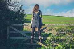 Young woman standing on gate in countryside Royalty Free Stock Image