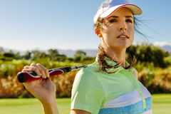 Young woman standing on golf course. Close up portrait of attractive female golfer holding golf club on field and looking away. Young woman standing on golf Royalty Free Stock Photos