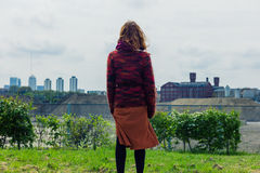 Young woman standing on grass and admiring the city Royalty Free Stock Image