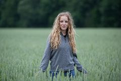 young woman standing in a green field Royalty Free Stock Images