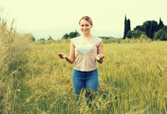 Young woman standing in green field Royalty Free Stock Image