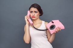 Freestyle. Woman standing on grey talking on stationary phone grimacing upset royalty free stock image